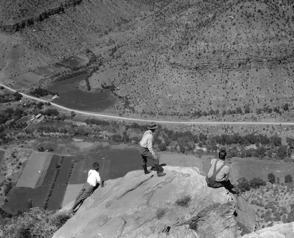 Eivind Scoyen, first superintendent of Zion National Park, Angus Woodbury, first ranger naturalist of Zion National Park, and Schieffer look down into valley from edge of rock on a Bridge Mountain hike