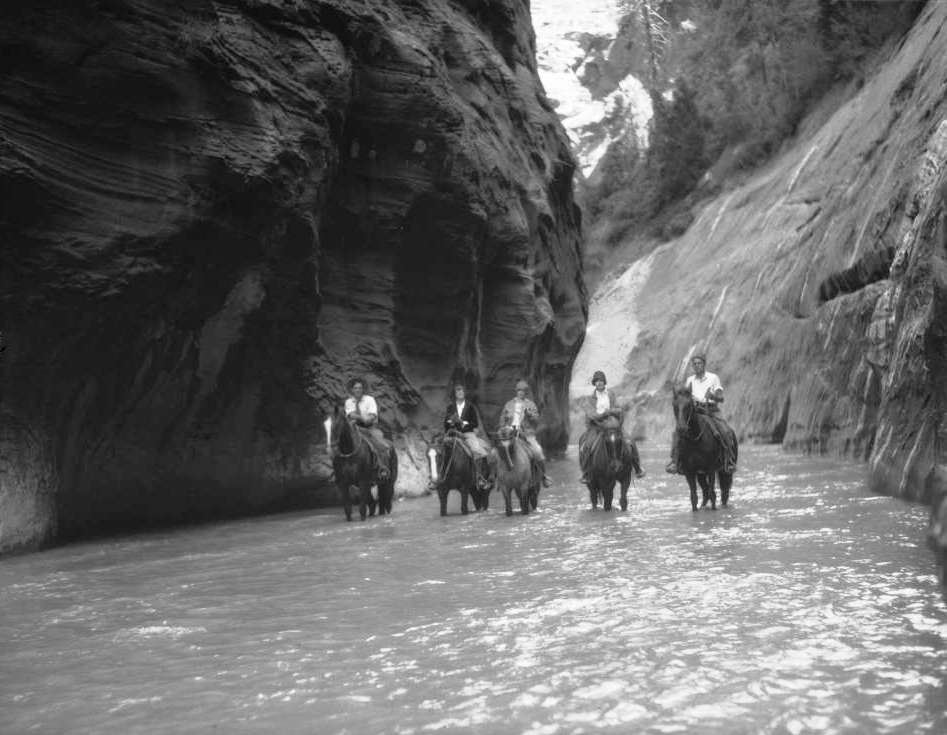 Walter Ruesch, Elsie Baer, Gertrude Grant, Lola Jackson and Vincent Hunter, Union Pacific Railroad photographer, travel on horseback through narrows at Zion National Park, Utah